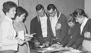 1950s students areound table with documents